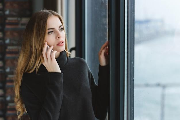 Belle jeune femme aux cheveux longs regardant par la fenêtre et parlant au téléphone portable