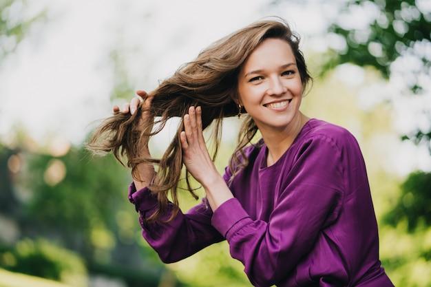 Belle jeune femme aux cheveux longs vêtue d'une robe violette tient ses cheveux