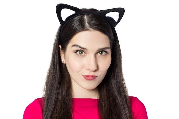 Belle jeune femme aux cheveux noirs blancs avec des oreilles de chat se penche sur fond blanc.