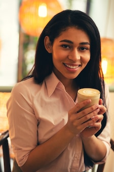 Belle Jeune Femme Aux Cheveux Noirs Dans Un Chemisier Rose Souriant à La Caméra Alors Qu'elle était Assise Avec Un Verre De Café Dans Les Mains Photo Premium