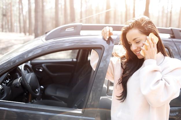 Une belle jeune femme aux cheveux noirs se tient près d'une voiture dans une forêt ou un parc. les mannequins féminins ont un voyage hors de la ville sur un crossover. elle parle au téléphone ou au smartphone