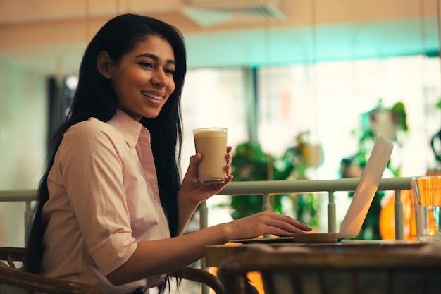 Belle jeune femme aux cheveux noirs tenant un verre de café et regardant loin avec un sourire alors qu'elle était assise devant un ordinateur portable