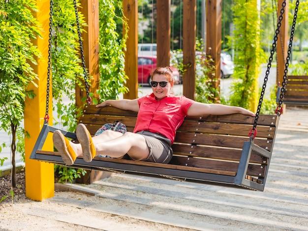 Belle jeune femme aux cheveux rouges assis sur un banc dans un parc de la ville, fille détendue