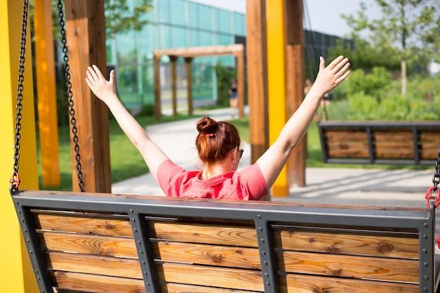 Belle jeune femme aux cheveux rouges assis sur un banc dans un parc de la ville, fille lève les mains, concept de bonheur