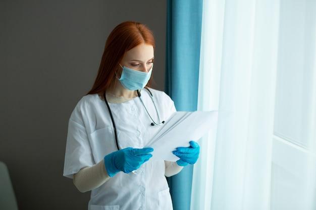 Belle jeune femme aux cheveux rouges dans une robe médicale et un masque