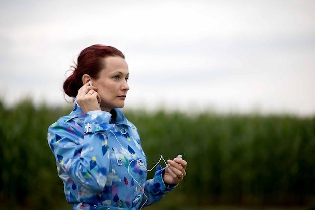 Belle jeune femme aux cheveux rouges, écouter de la musique avec des écouteurs