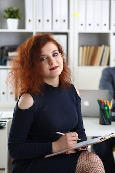Belle jeune femme aux cheveux rouges s'asseoir à table dans le bureau dans le cabinet de son patron tenir le stylo dans les bras