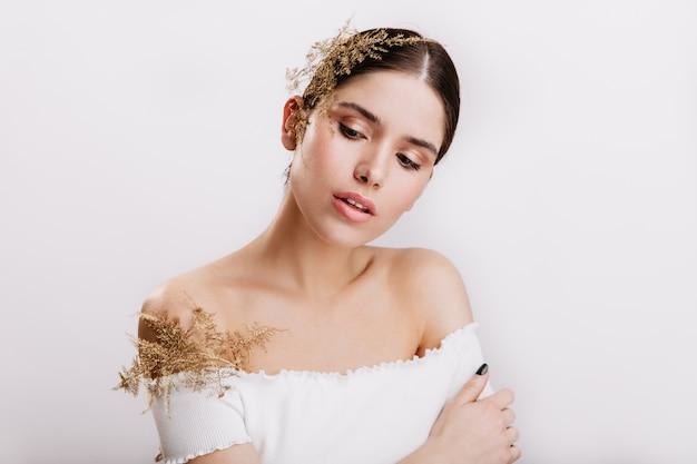 Belle jeune femme aux lèvres sensuelles regardant vers le bas avec embarras. une brune à la peau saine pose avec de belles plantes dans ses cheveux et son haut blanc.