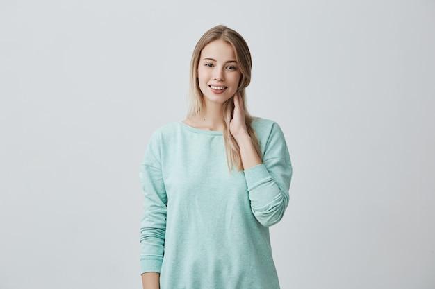 Belle jeune femme aux longs cheveux blonds soyeux et aux yeux sombres ayant des dents parfaites souriant de plaisir