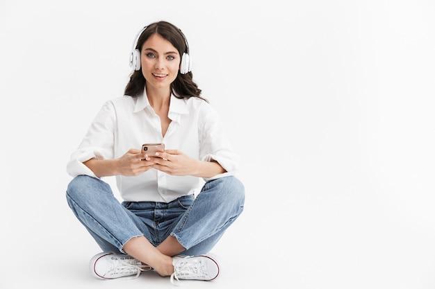 Belle jeune femme aux longs cheveux bouclés brune vêtue d'une chemise blanche assise isolée sur un mur blanc, appréciant d'écouter de la musique avec des écouteurs, à l'aide d'un téléphone portable