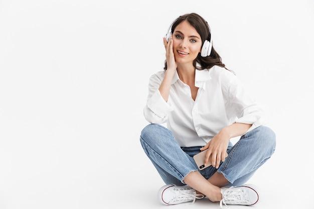Belle jeune femme aux longs cheveux bouclés brune vêtue d'une chemise blanche assise isolée sur un mur blanc, appréciant d'écouter de la musique avec des écouteurs