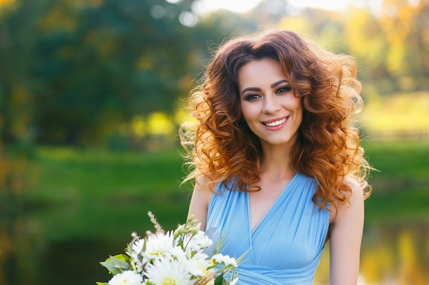 Belle jeune femme aux longs cheveux bouclés
