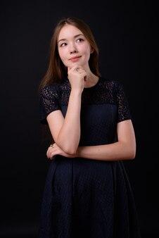 Belle jeune femme aux longs cheveux bruns contre le mur noir