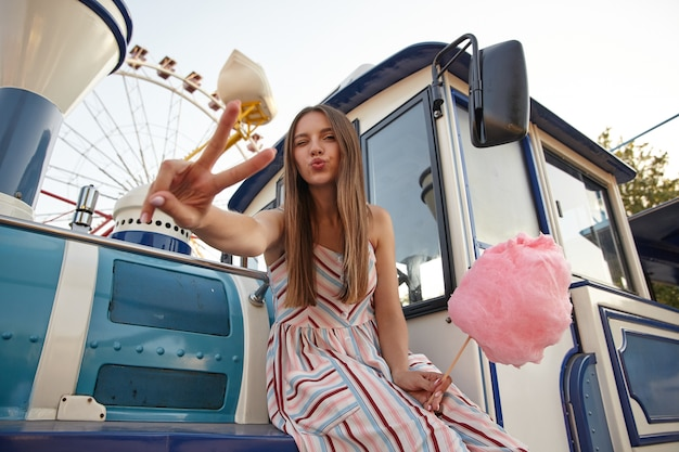 Belle jeune femme aux longs cheveux bruns posant sur des décorations de parc d'attractions sur une chaude journée ensoleillée, à l'oeil fermé et en levant la main avec le signe de la victoire