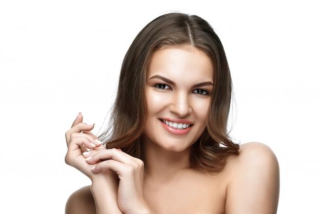 Belle jeune femme aux longs cheveux bruns et sourire blanc.