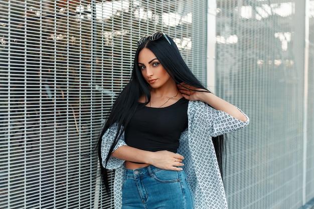 Belle jeune femme aux longs cheveux noirs avec une chemise blanche dans la rue