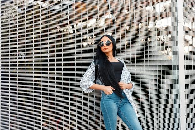 Belle jeune femme aux longs cheveux noirs dans des lunettes de soleil rondes à la mode