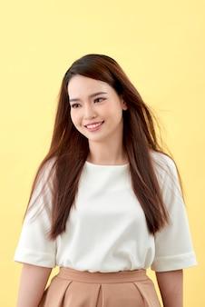 Belle jeune femme aux longs cheveux noirs posant sur fond jaune