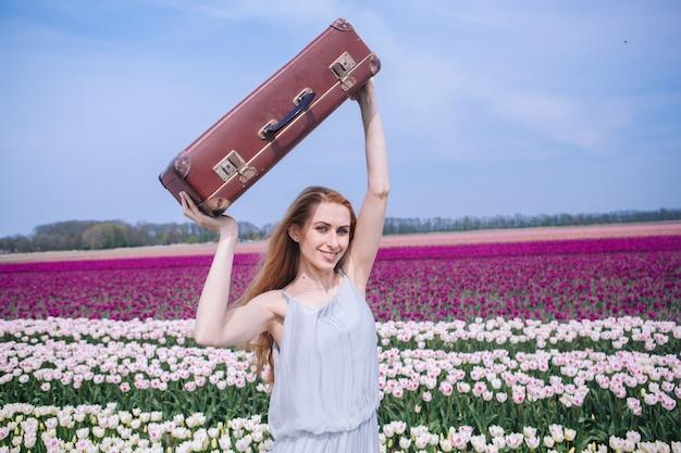 Belle jeune femme aux longs cheveux roux portant en robe blanche debout avec des bagages sur le champ de tulipes colorées.