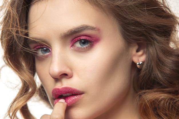 Belle jeune femme aux longs cheveux soyeux ondulés, maquillage naturel avec la main près du menton isolé sur mur blanc. modèle avec maquillage naturel.