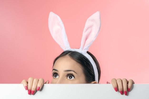 Belle jeune femme aux oreilles de lapin rose et affiche vierge sur rose.