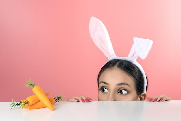 Belle jeune femme aux oreilles de lapin rose et carotte jouet sur rose.