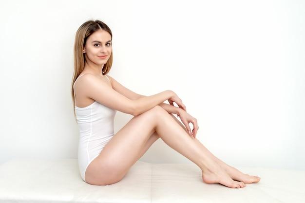 Belle jeune femme aux pieds nus en sous-vêtements en coton blanc assis sur fond blanc.