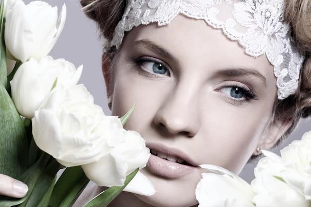 Belle jeune femme aux tulipes blanches
