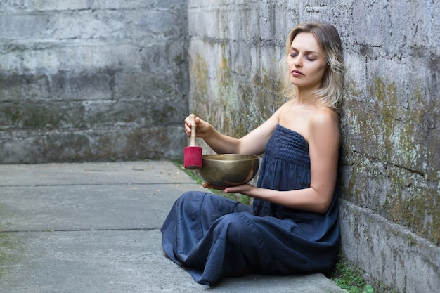 Belle jeune femme aux yeux fermés est assis et utilise un bol chantant.