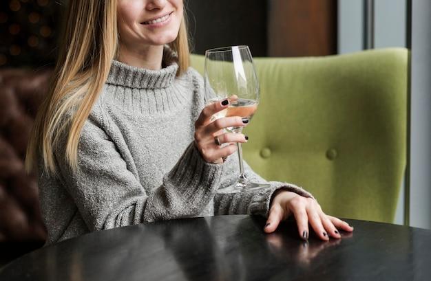 Belle jeune femme ayant un verre de vin
