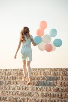 Belle jeune femme avec des ballons multicolores volants contre le ciel. concept de bonheur et de rêves