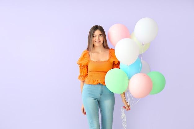 Belle jeune femme avec des ballons sur une surface de couleur