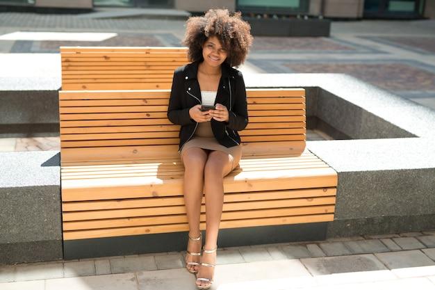 Belle jeune femme sur un banc en été avec un téléphone mobile