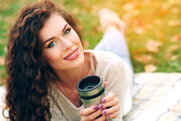 Belle jeune femme avec de beaux cheveux bouclés boit du thé dans une tasse thermo à l'automne dans le parc et se trouve sur une couverture et se penche sur la caméra