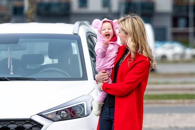 Belle jeune femme avec un bébé sur ses mains à côté d'une voiture blanche, la joie d'être ensemble