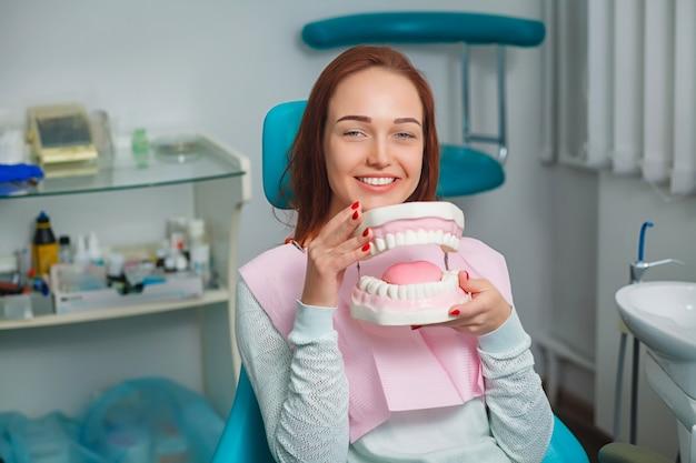 Belle jeune femme avec de belles dents blanches, assis sur un fauteuil dentaire et tenant une prothèse dentaire en plastique dans une boîte.