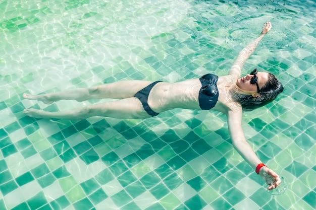 Belle jeune femme en bikini noir se détendre dans la piscine de l'hôtel