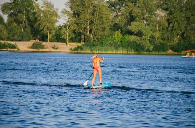Belle jeune femme en bikini sur une planche de sup dans la rivière