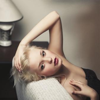Belle jeune femme blonde allongée sur un canapé