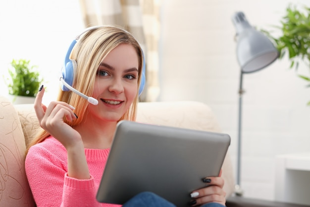 Belle jeune femme blonde assise sur le canapé dans le salon tenir la tablette dans les bras écouter de la musique ensoleillée