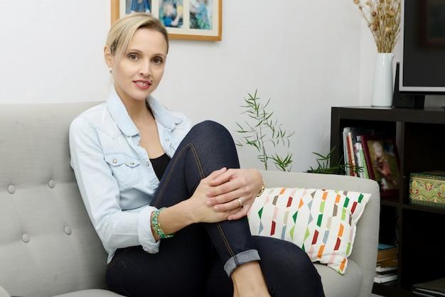 Belle jeune femme blonde assise sur le canapé