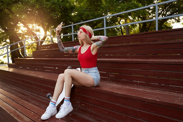 Belle jeune femme blonde aux bras tatoués dans un t-shirt rouge et un short en jean avec un bandana tricoté sur la tête, dans des lunettes rouges, tenant un smartphone et fait selfie