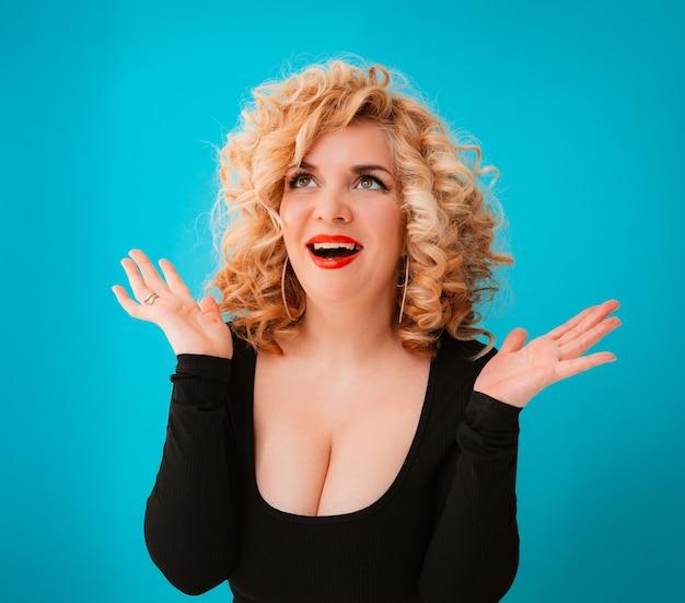 Belle jeune femme blonde aux cheveux bouclés, plus la taille du corps positif avec de gros seins