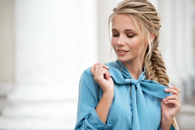 Belle jeune femme blonde aux cheveux tressés en plein air. fille en robe bleue se promène dans les rues de la ville.