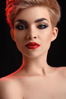 Belle jeune femme blonde aux lèvres rouges posant