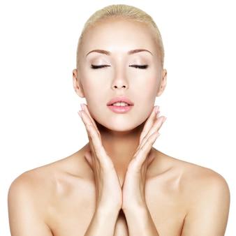Belle jeune femme blonde aux yeux fermés et les mains au visage de la santé