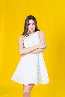 Belle jeune femme blonde en belle robe de printemps, posant sur jaune