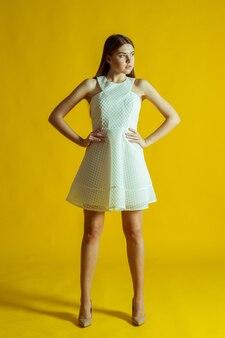 Belle jeune femme blonde en belle robe de printemps, posant sur une surface jaune en studio