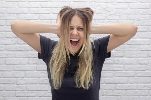 Une belle jeune femme blonde caucasienne tient sa tête, hurle et se couvre les oreilles avec ses mains. désespoir, frustration, maux de tête, migraine, épuisement, dépression émotionnelle, voix dans la tête, peur