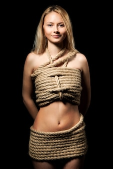 Belle jeune femme blonde avec un corps recouvert de cordes restant et regardant la caméra sur fond noir. jeux sexuels et pratique du concept bdsm